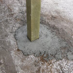 Close-up of post set in concrete