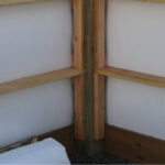 Photo of inside corner, pressure-treated base girts, and wall insulation